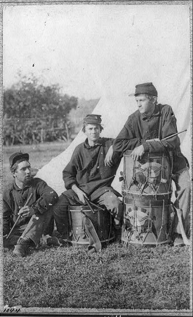 Three soldiers in camp with drums